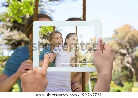 Hand holding tablet pc showing mother pushing her daughter on a swing - stock photo