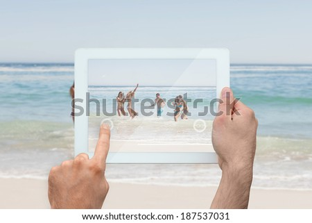 Hand holding tablet pc showing young friends having fun at the beach - stock photo
