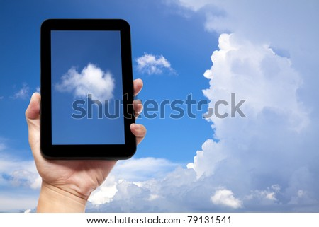 hand holding tablet pc with cloud background - stock photo