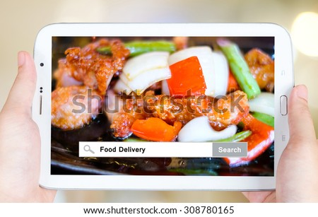Hand holding tablet with food delivery words on search bar over food  background, food online, food delivery concept - stock photo