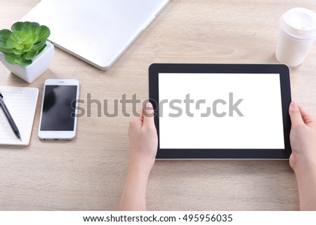 Hand holding tablet with smartphone and laptop on wooden desk, Tablet mockup for webdesign and user interface