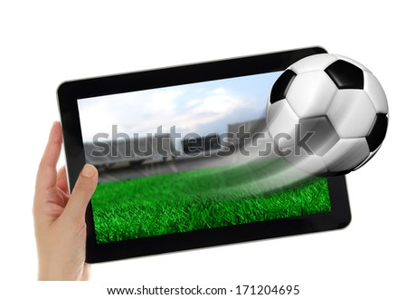 Hand holding tablet with soccer ball flying off screen  - stock photo