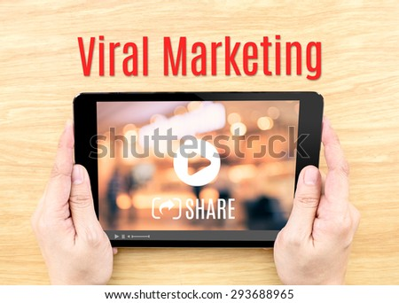Hand holding tablet with Viral marketing word on wood table ,Internet business concept. - stock photo
