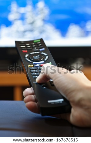Hand holding television remote control pressing buttons - stock photo