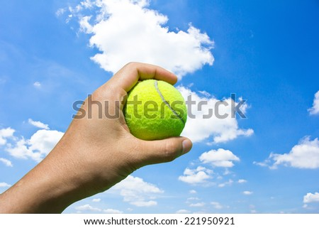 Hand holding tennis ball on blue sky background - stock photo