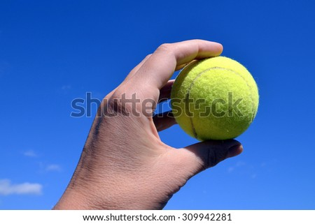 Hand holding tennis ball on blue sky background.