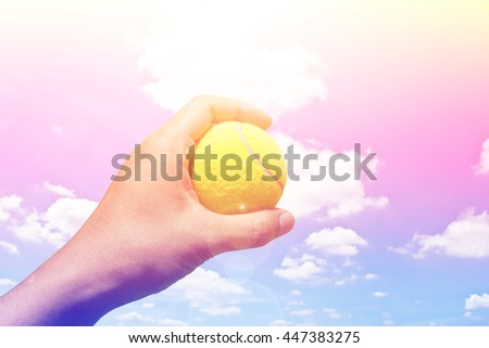 Hand holding tennis ball with color filters - stock photo
