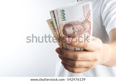 Hand holding Thai baht notes on white background