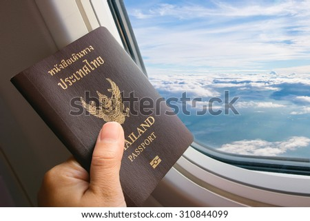 hand holding Thailand passport on airplane window - stock photo