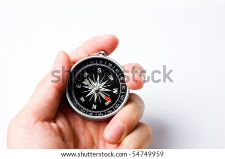Hand holding the black compass isolated on white. - stock photo