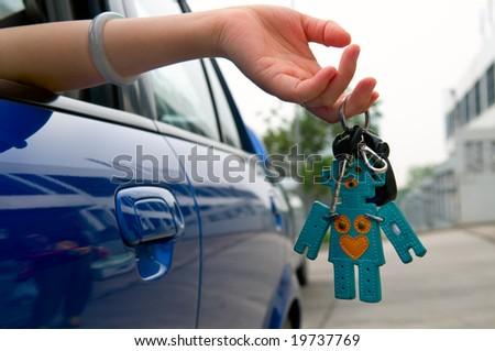 Hand holding the car key with lovely key ring - stock photo