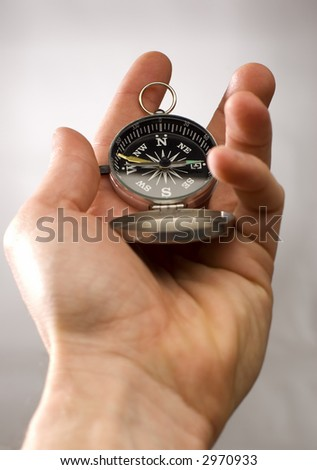 Hand holding the compass close up shoot