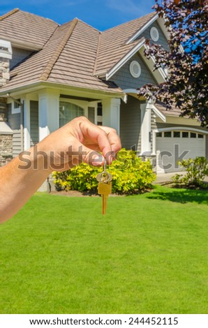 Hand holding the keys for a big custom made luxury house for sale, house of dream in the suburbs of Vancouver, Canada. Vertical. - stock photo
