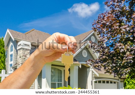 Hand holding the keys for a big custom made luxury house for sale, house of dream in the suburbs of Vancouver, Canada. Horizontal. - stock photo