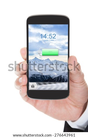Hand Holding The Mobile Phone With Charged Battery Over White Background