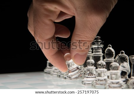 Hand holding the  pawn to make the first move - stock photo