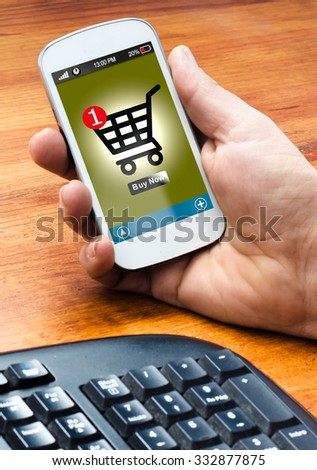 hand holding the smartphone and makes online shopping, (shopping cart and buy button on the screen) - stock photo