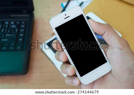 Hand holding the smartphone with desk - stock photo