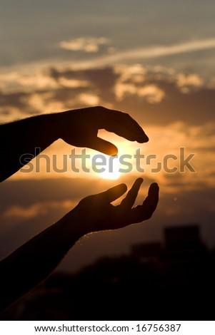 Hand holding the sun - stock photo