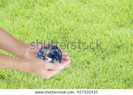 hand holding the world against blur of green background, human hands with healthy world concept, love and safe conception.Elements of this image furnished by NASA - stock photo