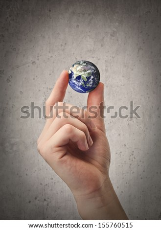 hand holding the world with two fingers - stock photo