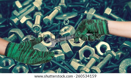 hand holding the wrench on used nut and bolts for equipment industrial background - stock photo