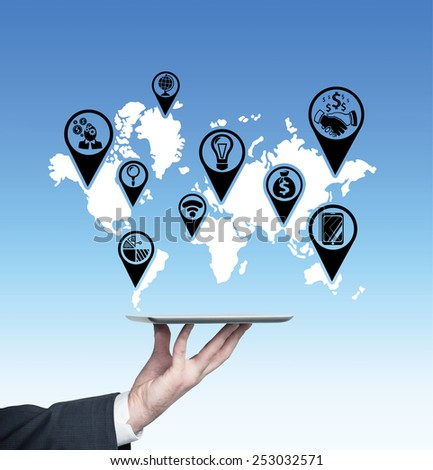hand holding touch pad with icons on world map - stock photo