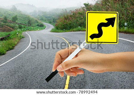 Hand holding traffic sign on curve road - stock photo