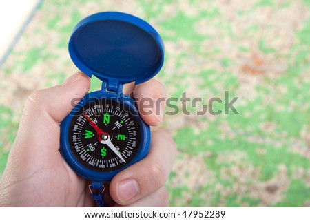 Hand holding travel north direction compass on map - stock photo