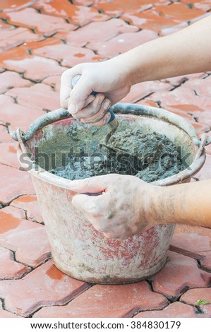 Hand holding trowel mixing mortar in a bucket