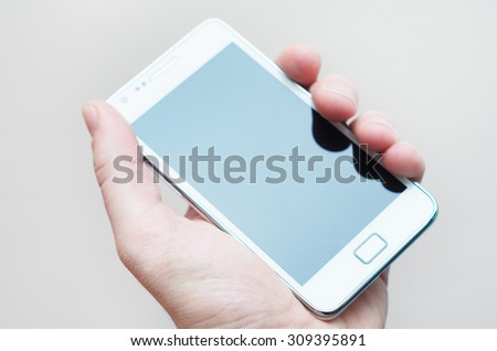 Hand holding turned off smartphone - stock photo