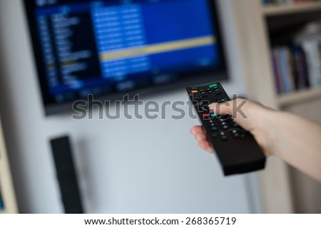 Hand holding tv remote control directs him toward the TV and changes the settings - stock photo