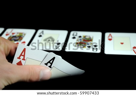 hand holding two aces cards and board with five cards isolated on black - stock photo