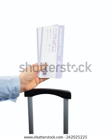 Hand holding two air tickets with the suitcase on white background - stock photo