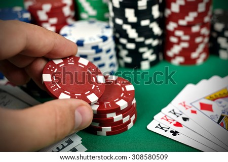 hand holding two color poker chips, close up - stock photo