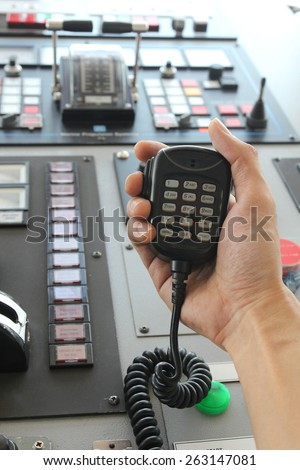 Hand holding two way radio receiver on bridge of ship  - stock photo