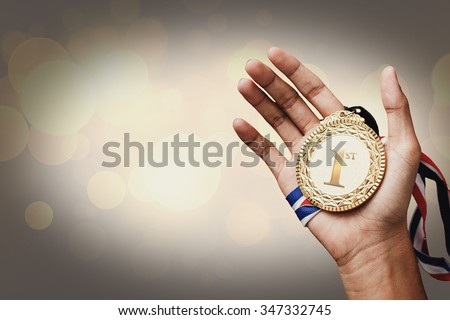 hand holding up a gold trophy cup/ medal as a winner in a competition - stock photo