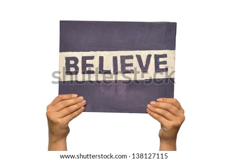 Hand holding up a self painted text Believe isolated on white - stock photo