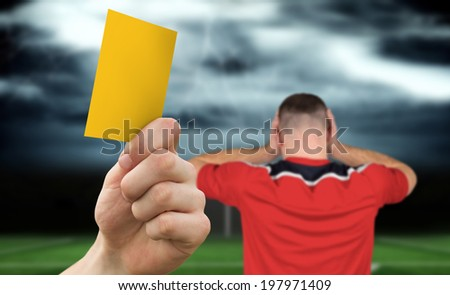 Hand holding up yellow card against football pitch under stormy sky and player - stock photo