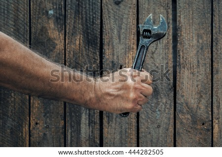 Hand holding vintage adjustable wrench on a wooden background