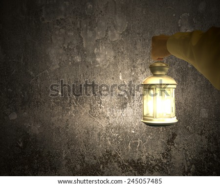 Hand holding vintage lamp illuminating dark concrete wall background