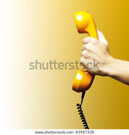 Hand holding vintage telephone receiver isolated over yellow background - stock photo