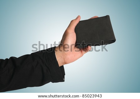 Hand holding wallet, isolated on blue