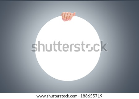 Hand holding white, blank circle plaque or poster. - stock photo