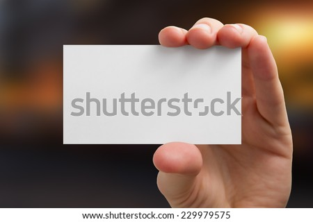 Hand holding white business card on blurred background - stock photo