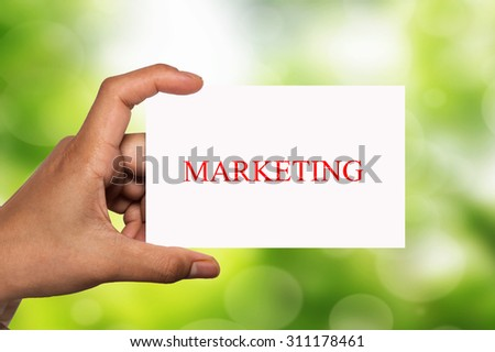 hand holding white card written marketing over blur background - stock photo