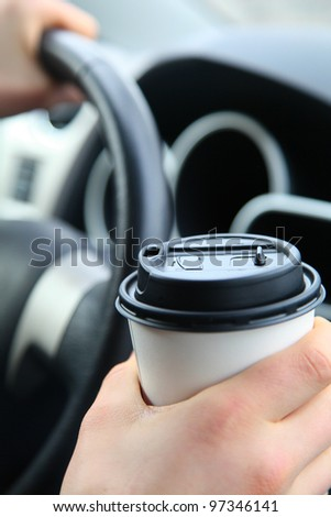 Hand holding white coffee cup on the steering wheel background. Shallow Focus - stock photo