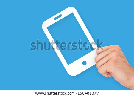 Hand holding white, empty, blank mobile phone cardboard, isolated on blue background. - stock photo