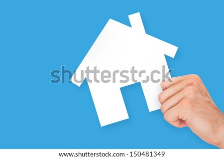 Hand holding white, empty, blank real estate cardboard, isolated on blue background. - stock photo
