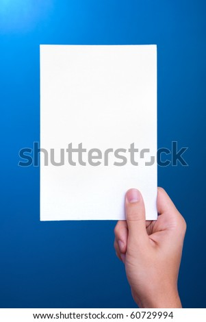hand holding white greeting paper card on blue background
